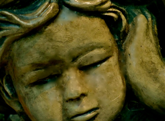 Yearning expression on stone scupture of child