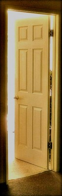 Cream colored door ajar, revealing white light